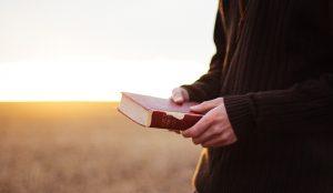 Segurando a Biblia para receber revelação