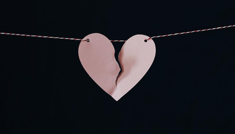 Coração de papel sendo rasgado no meio