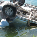 missionários abrindo porta de carro submerso